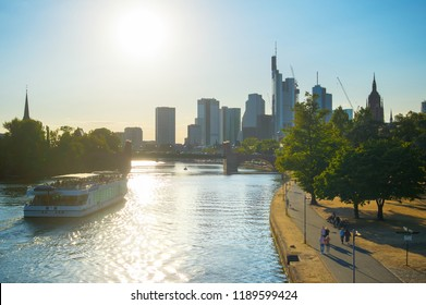 Financial district, cruise boat and people walking at embankment of the river Main at sunset. Frankfurt, Germany