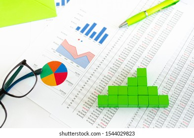 Financial documents, with green cubes arranged in a column graph