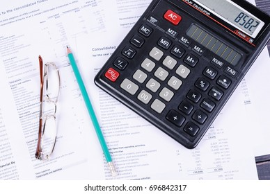 Financial documents lying on their black calculator, glasses and pencil
