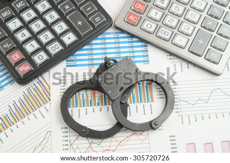 Financial fraud concept, calculators and handcuffs on financial documents