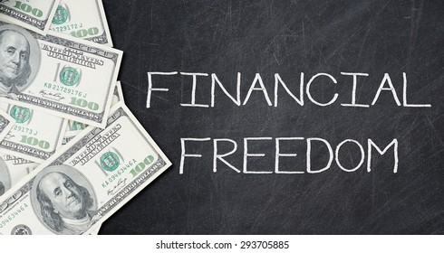 FINANCIAL FREEDOM text on a black chalkboard with a number of one hundred US dollar notes