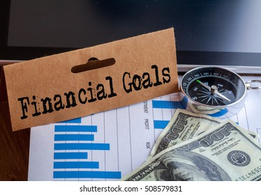 Financial Goals Words on tag with dollar note,smartphone,compass and graph on wood backgroud,Finance Concept