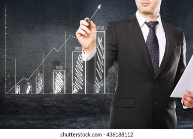 Financial growth concept with businessman holding document and drawing abstract business chart on dark concrete and city background