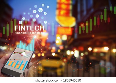 Financial growth graph on smart phone and currency symbol on night city life china town background. Artificial intelligence innovation machine learning concept and financial technology idea
