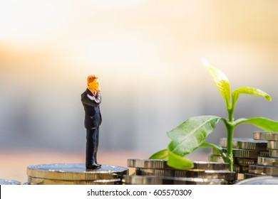 Financial Growth. Miniature people : Small businessman figure thinking/standing on pile of coins with plant using as background.