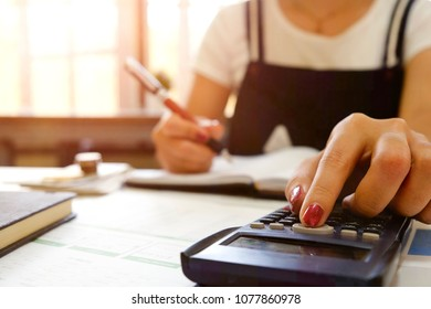 Financial home, closeup woman calculate on calculator and writing on paper with report finance data in paper.