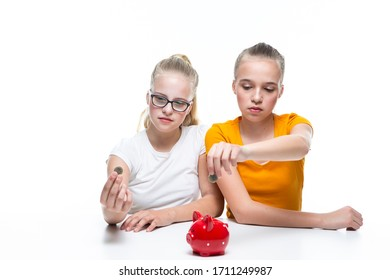 Financial Ideas and Concepts. Portrait of Caucasian Teenager Twin Girls Posing With Coins and Piggy Bank. Storing Up Money For Savings. Horizontal Image