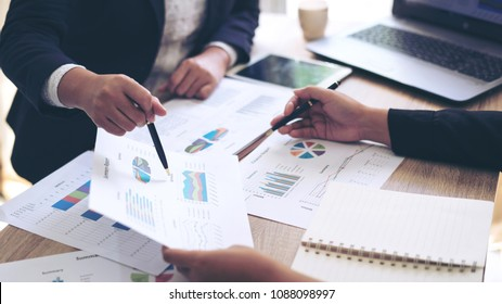 financial Image of two  business people pointing at business document presentation summary report , during discussion at meeting , Notebook on wood table