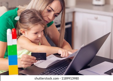 financial issues – Young mother calculating finances at home with cute daughter