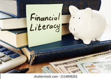 Financial Literacy written on a stick and piggy bank as savings symbol.