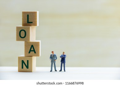 Financial loan negotiation / discussion among a lender and borrower concept : Miniature figurine two businessmen talk on money loan contract agreement, discuss about a company credit and loan profile