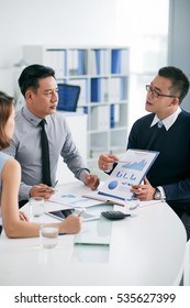 Financial manager explaining business chart to coworkers at meeting
