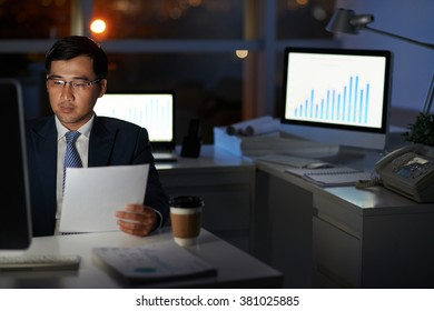 Financial manager working alone in empty dark office