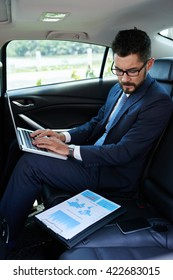 Financial manager working on report when sitting in car