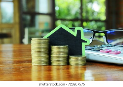 Financial mortgage loan concept with gold coins stack and wood house sign on wooden table backgrounds