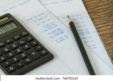 Financial office salary man or tax calculation concept as black calculator and pencil on salary slips with numbers.