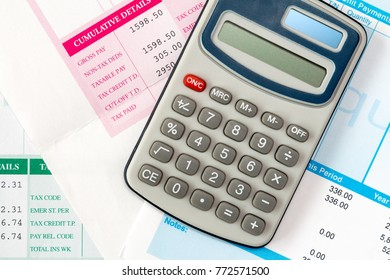 Financial office salary or tax calculation concept by calculator on pile of salary slips
