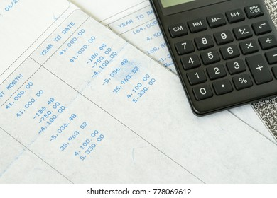 Financial office salary tax calculation with salary revenue slips with numbers and calculator put on table.