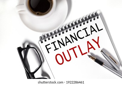 Financial Outlay. text on white notepad paper on white background. near a cup of coffee