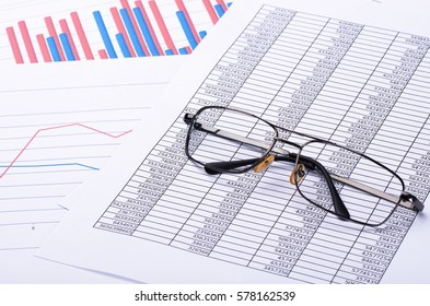 Financial paper charts and graphs and glasses. Business reports and pile of documents.