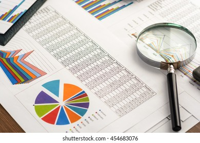 Financial paper charts and graphs on the table.