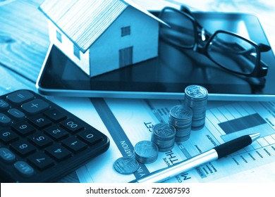 Financial paper and work station and house model  with tablet on working table, business concept.