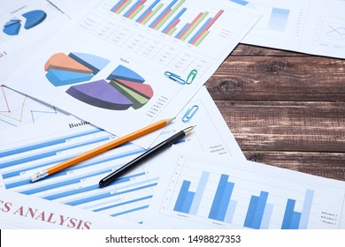 Financial papers with graph and charts on wooden table