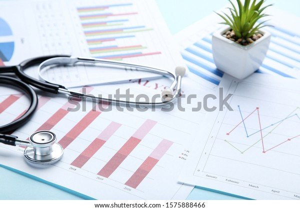Financial papers with stethoscope and green plant in pot