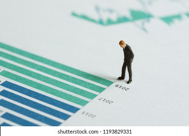 Financial performance report analysis or investment concept, miniature people figure success businessman leader standing and thinking on printed company yearly revenue graph and chart document.