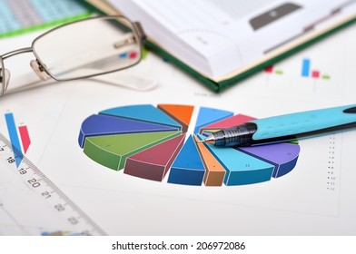financial pie  chart on table with glasses and pen