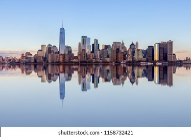 Financial place in the Lower Manhattan, view from a boat with clear reflection in the water