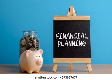 Financial Planning, financial concept. Mason jar with coins inside, piggy bank and chalkboard on wooden table.