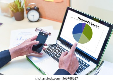 Financial Planning Concept,man is working by using a laptop with finger pointer at computer screen and holding a smart phone on wooden table.