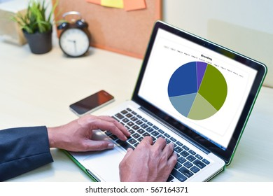 Financial Planning Concept,man is working by using a laptop with smart phone, wooden table.