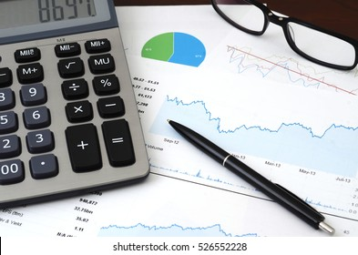 Financial Planning or SEO (Internet marketing) Concept - Sales or Visitors Report and Graphs Analysis. Colorful sales charts, graph, calculator, pen and glasses.