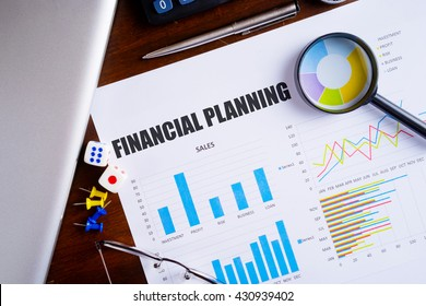 """""""Financial Planning"""" text on paper sheet with magnifying glass on chart, dice, spectacles, pen, laptop and blue and yellow push pin on wooden table - business, banking, finance and investment concept"""