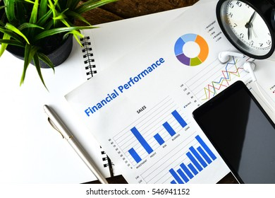 """""""Financial Planning"""" text on paper sheet with smartphone on chart clock,compass, pen,earphones on wooden table - business, banking, finance and investment concept"""