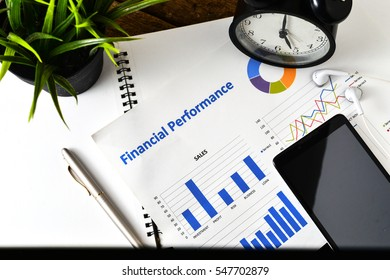 """""""Financial Planning"""" text on paper sheet with smart phone on chart clock,compass, pen,earphones on wooden table - business, banking, finance and investment concept"""