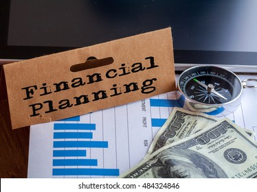 Financial Planning Words on tag with dollar note,smartphone,compass and graph on wood background,Finance Concept