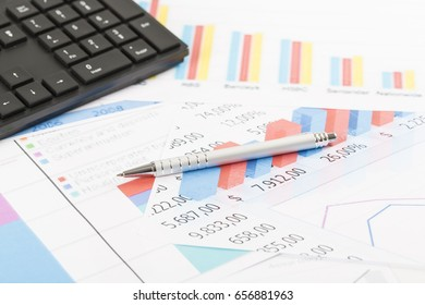 Financial printed paper charts, graphs on desk with pen and keyboard