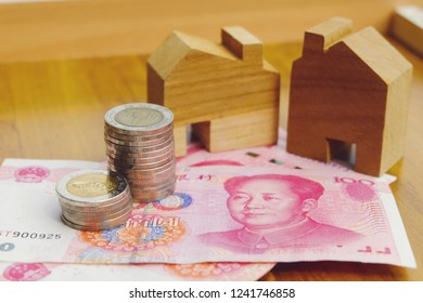 Financial property investment in and house mortgage in China concept. stacks of coins, Chinese yuan and wooden hand made house model on wooden background.