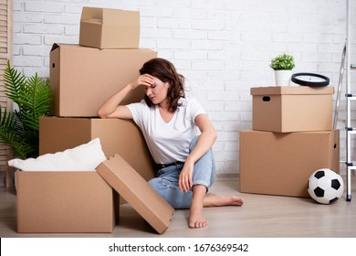 financial or relationship problems - young stressful woman sitting with cardboard boxes ready to moving day