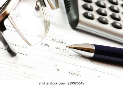 Financial report. Calculator and pen on a business background.