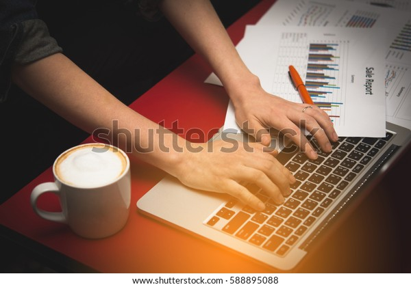 Financial report with chart and data on a laptop with business woman's hands at work