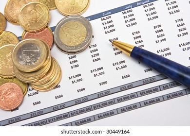 Financial report with pen and heap of coins
