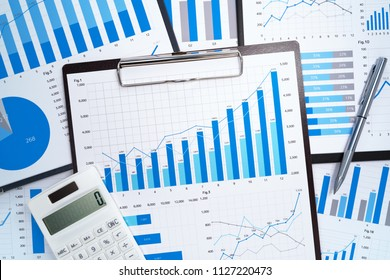 Financial reports. Analyzing and gathering statistical data. Many blue growth charts, calculator and pen.