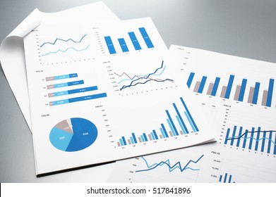 Financial reports. Graphs and charts. Documents on gray reflection background.