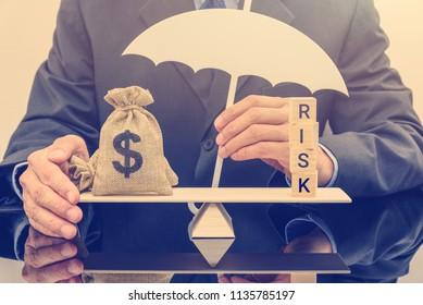 Bewertung des finanziellen Risikos/Risikomanagement und Schutz des Portfolios: Geschäftsmann hält einen weißen Regenschirm, schützt eine Dollartasche auf Basis-Saldo-Skala, verteidigt Geld vor Betrug oder Betrug