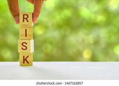 Financial risk assessment and portfolio risk management concept : Stack of vertical 4 cubes on a table with a letter R, I, S, K on each cubes, depicts managing / control asset risk to gain high return