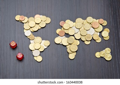 Financial risk. Office desk with world map made of money coins and two red dices